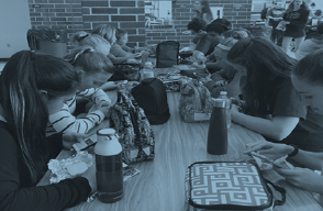 Many tables of students spend their time playing on their phones and checking social media during lunch.