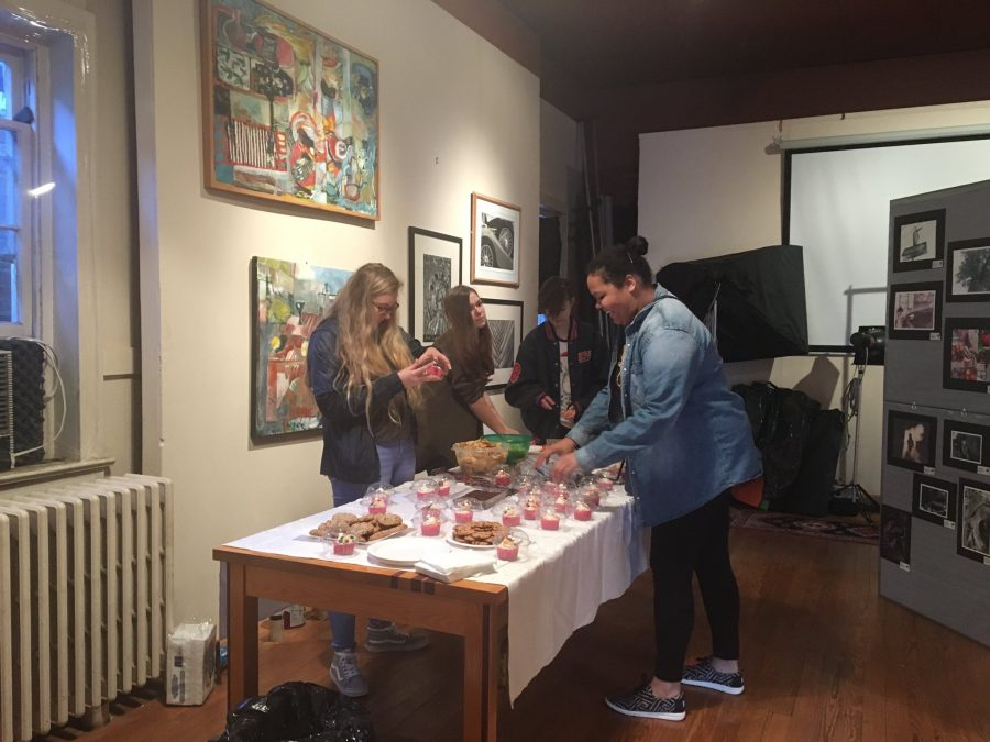 Seniors Colleen Cragun and Arleena Allen prepare a table full of goodies for visitors at the artwork showing on Main Street. The creations from multiple students were displayed on the walls.
