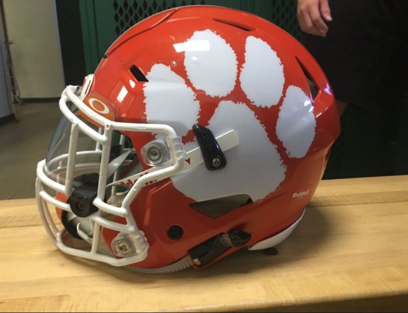 Before a game, senior Andrew Pickett's helmet sits on a locker room bench.