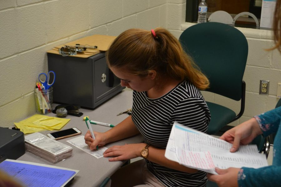 Writing a receipt for a deposit, junior Stephanie Scheffer diligently works her shift in the newly opened Cougar Branch.
