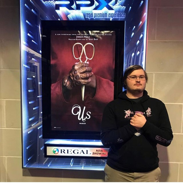 Posing in front of the movie poster, Senior Connor Roy prepares to see the new horror movie, Us.
